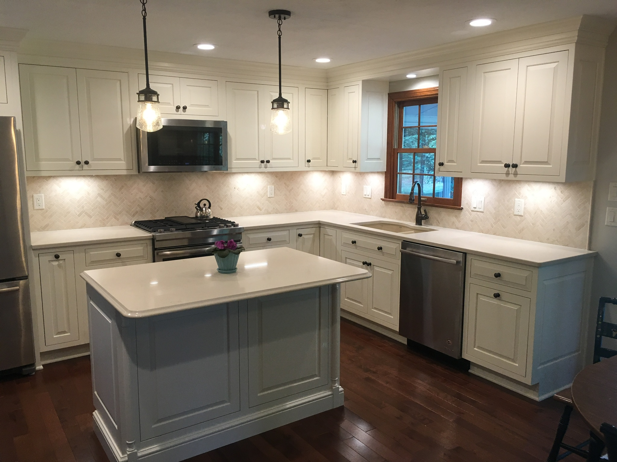 Modern kitchen with white stone countertop and white wooden cabinetry